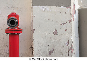Red metallic vintage hydrant, fire-cock, with a round gray hole against background of a white old cracked wall.