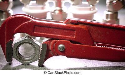 Red metalwork adjustable spanner for sanitary works against...