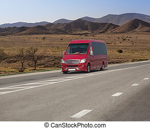 Red minibus moves on a road in the mountains on a summer day