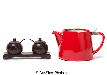 Red modern teapot and wooden containers to put the sugar, salt and other.