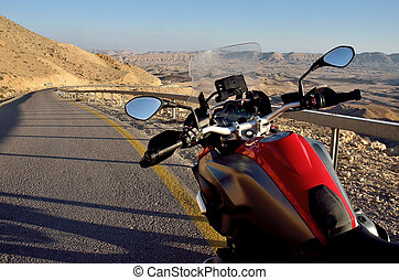 Red motorbike on the road in Negev desert near Big crater, Israel, Middle East