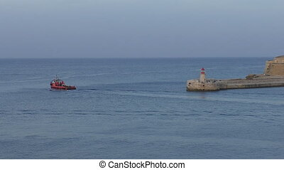 Red motorboat passing lighthouse