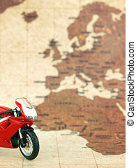 Red motorcycle in front of a world map