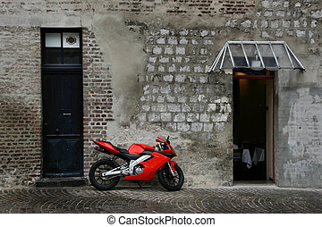 Red, new, fast motorcycle parked in old town street of Amiens, Picardy, France