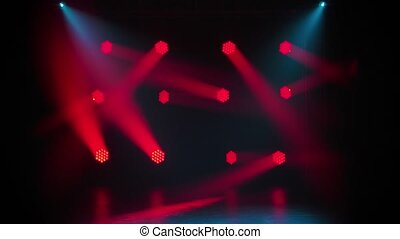 Red moving spotlights and blue beams on an empty stage in the dark. Stage lighting. Dynamic light show. The lights are shining on disco party, wedding or birthday celebration, or at nightclub entertainment.
