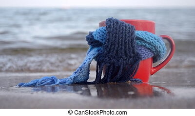 Red mug with coffee tied with blue knitted scarf stands on sandy beach of ocean sea waves. Concept warm mood travels relax ocean sea vacation holiday rest