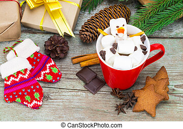 Red mug with hot chocolate with melted marshmallow snowman on wooden background with gifts and Christmas decorations