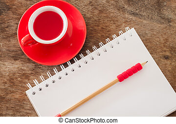 Red mug with open notebook, stock photo
