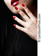 Close up of womans red nails, lips and long black hair
