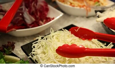 red nippers take portion of cabbage from salad bar close up