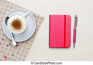 Red notebook with pen and coffee on wooden
