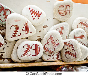 red numbers drawn on white stones