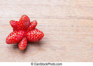 Red odd strawberry fruit on wooden table. - Healthy ...