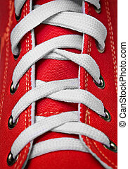 Red old-fashioned gym shoe - lacing - On red old-fashioned...