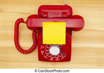 Red old retro rotary landline phone with sticky note