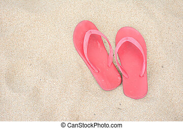 Red old slippers on the beach
