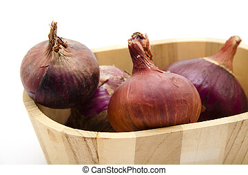 Red onion in wooden bowl