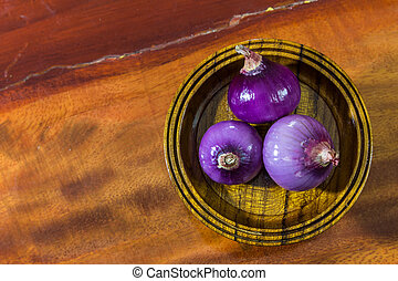Red onion on wood background