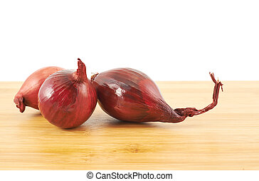 Red onions composition over a wooden table
