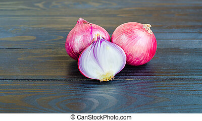red onions on black wooden background