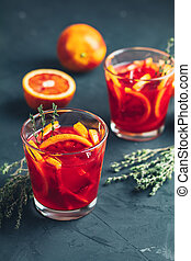 Red orange juice in a large glass on dark concrete background
