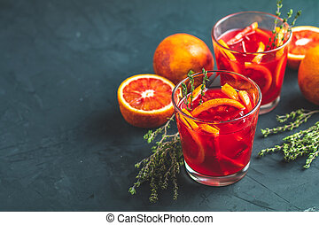 Red orange juice in a large glass or blood orange sparkling vodka cocktail or aperitif with campari