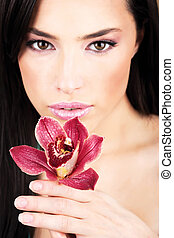 Red orchid in hands