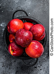 Red organic nectarines in a colander. Black background. Top view