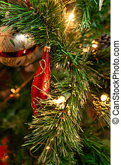 Red ornament on green Christmas tree