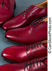 Red oxford shoes on blue background. Three pair brogues....