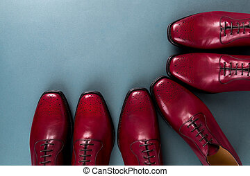 Red oxford shoes on blue background. Three pair brogues. Top...