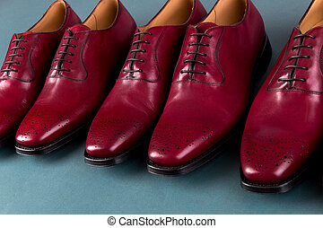 Red oxford shoes on blue background. Three pair brogues. -...