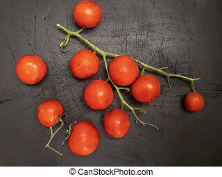 red pachino tomatoes grape on a b?ack wooden background. Italian protected geographical indication product from Sicily