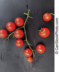 red pachino tomatoes grape on a b?ack wooden background.