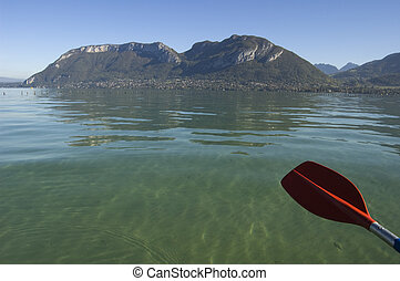 Red paddle of canoe, water and mountains of Annecy lake, in France, Europe