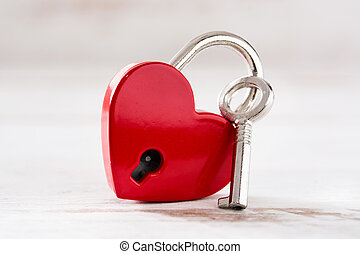 Red padlock hearts with key on white wooden background.