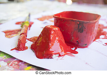 Red paint and paint brush at manual arts workshop for children