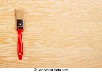 red paint brush on a wooden background
