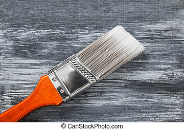 Red paintbrush on gray painted background