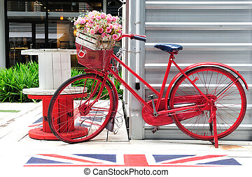 Red painted bicycle with a bucket of colorful flowers
