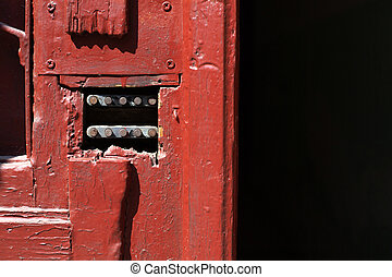 Red painted wooden door with a code lock