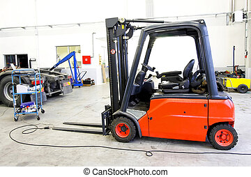 Red palette lifter - Red forklift vehicle in truck service...