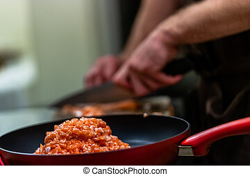 Red Pan with Pile of Cutted Salmon Pieces in the Foreground, Male Chef Cutting Fresh Salmon on the Wooden Board in the Background