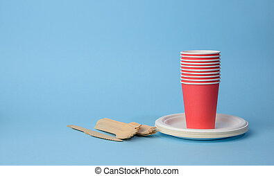 red paper cup, white plates and wooden forks and knives on a blue background. Plastic rejection concept