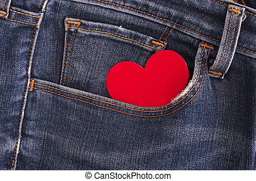 Red paper heart in a pocket of blue jeans