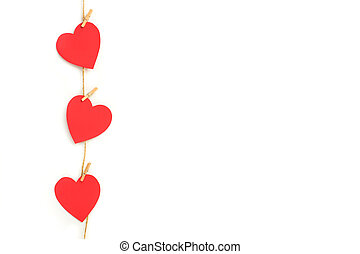 Red paper hearts hanging by a sisal yarn on a white background with copy space
