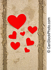Red paper hearts in beach sand