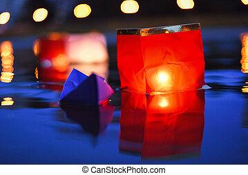 Red paper lanterns floating in dark water at night
