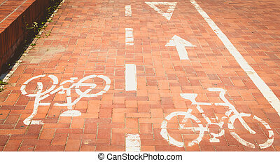 red paved bike path or a bike is painted in white paint