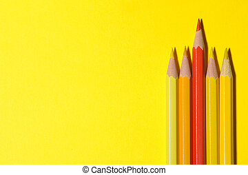 Red pencil among yellow ones on a bright yellow background. the concept of individuality. top view. space for text